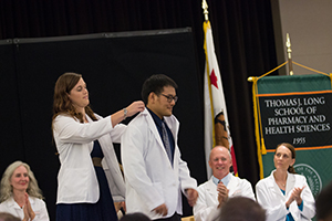 Class of 2016 member is cloaked with his white coat by his second-year buddy.