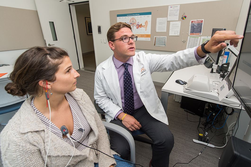 Jacob Blaschko-Iveland, a doctor of audiology student in San Francisco, explains the test results to a patient, June 21, 2017.